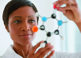 Woman looking at plastic model of molecule